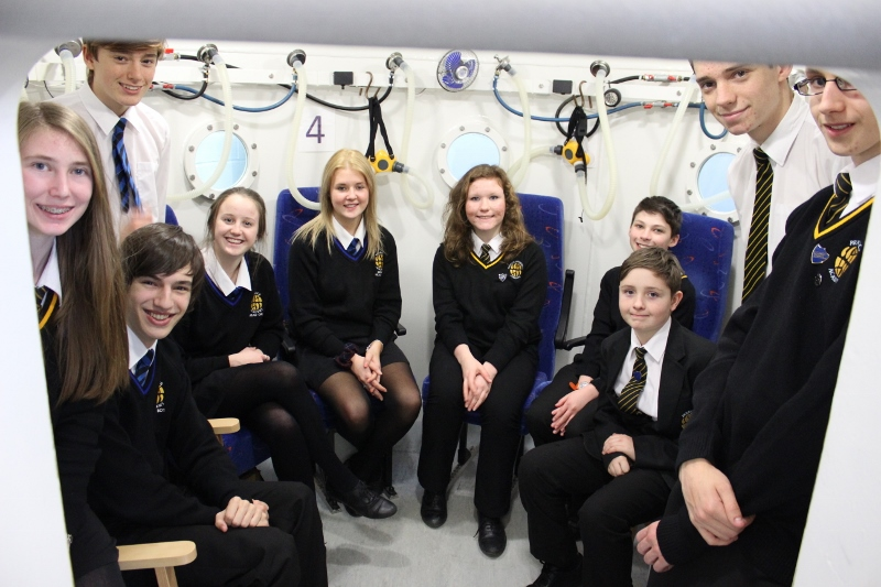 Students pose in a therapy chamber at Merlin MS Centre