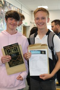 two students with GCSE results certificates